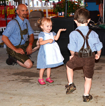 Debbie Blank | The Herald-Tribune<br /> Leo (from right), 4, and Cora, 2, Clark practice their fancy footwork to music by Pros't on the main stage Friday night as dad Dan, Burlington, watches.