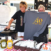 Debbie Blank | The Herald-Tribune<br /> In a brats and metts booth, Carol Dobson (right) shows the 2016 T-shirt to Teresa Fitzpatrick.