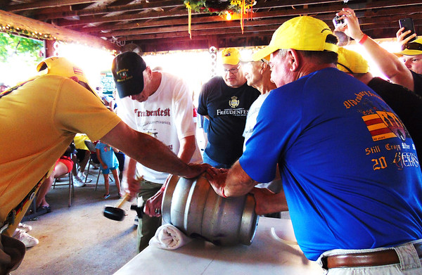 Debbie Blank | The Herald-Tribune<br /> Ed Hoelker, 93, Oldenburg, had the honor of tapping the first beer keg to open the party. Watching (from left) are fest chair Gary Muchel and steering committee members Paul Selkirk and Jeff Paul.