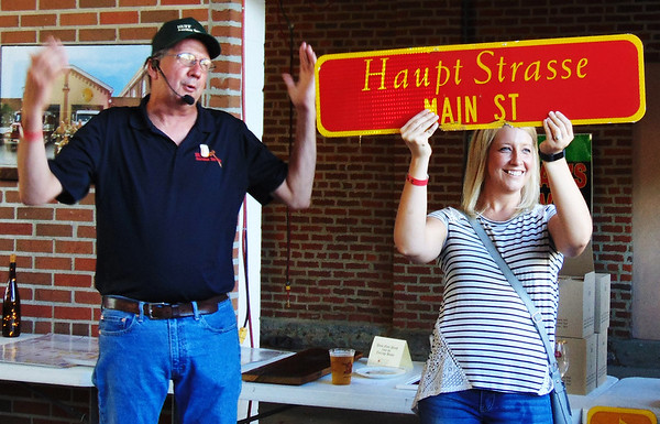 Debbie Blank | The Herald-Tribune<br /> Auctioneer Roger Huff (left) gets the bidding up for a Main Street sign with the help of daughter Jeanine at the 10th live auction.