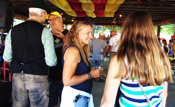 Debbie Blank | The Herald-Tribune<br /> Fest chairman Gary Munchel and Lisa Gausman chat with friends after opening ceremonies concluded Friday evening.