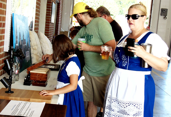 Debbie Blank | The Herald-Tribune<br /> Carrie Weberding (from right), Oldenburg, cousin-in-law Tom Weberding, Batesville, and her daughter Bella, 8, check out live auction items. Donations ranged from a table crafted from old Oldenburg lumber to an early 1900s view of the village.