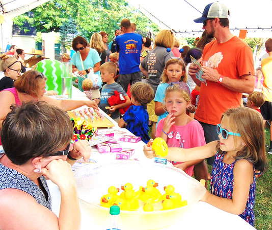 Debbie Blank   The Herald-Tribune<br /> Kids were kept occupied by stilt walkers who juggled and made balloon animals, a variety of treats and games under a tent and on the church lawn.