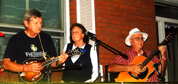 Debbie Blank | The Herald-Tribune<br /> Joe (from left) and Betsy Bauer and another Happy Valley Bluegrass Band member entertain from a Pearl Street porch to keep musical instruments out of the spotty rain early Friday evening.