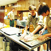 Debbie Blank | The Herald-Tribune<br /> Troop 634 Boys Scouts (from right) Quinn Rasnick, a quartermaster, and Joe Hartman, who's working toward his Eagle Scout award, prepare to bake cinnamon rolls under the watchful eyes of leader Ken Rudolf at Saturday's Freudenfest breakfast in the Holy Family Catholic Church cafeteria. The troop has been organizing the breakfast during the fest since 1996.