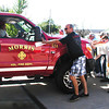 Diane Raver | The Herald-Tribune<br /> AFTER THE NEW FIRE TRUCK was blessed by Father Shaun Whittington, community members pushed the vehicle into the fire house. This tradition dates back over 100 years, the priest said. After a fire truck was used for the first time, many people would help push it into the fire house bay to symbolize their support for the important work firefighters do.
