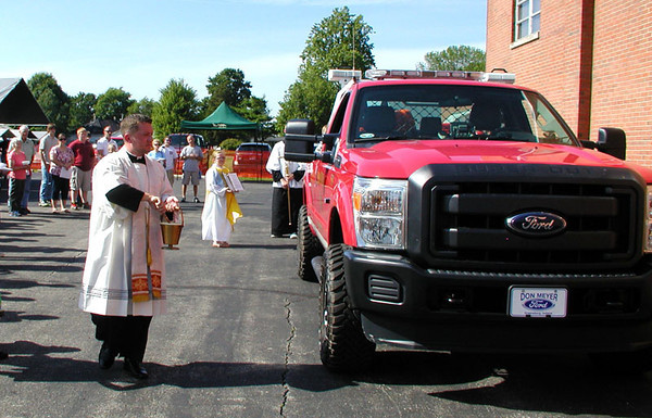 Diane Raver | The Herald-Tribune<br /> DURING THE MORRIS Firemen's Festival June 21, Father Shaun Whittington blessed the new brush truck.