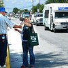 Debbie Blank | The Herald-Tribune<br /> An FCN Bank employee distributes beads to spectators.