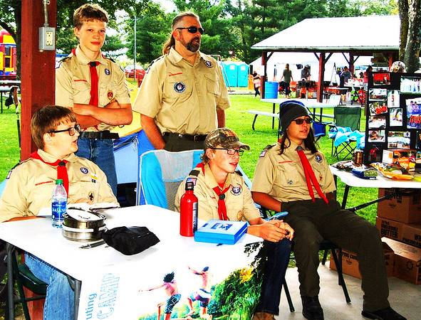 Debbie Blank | The Herald-Tribune<br /> Troop 646, New Alsace, Boy Scout (clockwise from seated right) Kaeran Draude, 15; James Bulach, 14; Dominic Martini, 12; and Theo Martini, 16; and leader Keith Millson try to get spectators interested in buying their fundraising popcorn at the Sunman Fall Fest booths tent.