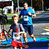 Debbie Blank | The Herald-Tribune<br /> Mason Barnes, 8, Hamilton, Ohio, crosses the finish line with dad Steve.