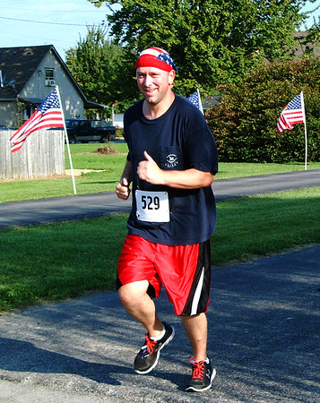 Debbie Blank | The Herald-Tribune<br /> It just felt right for Bryan West, St. Leon, to put on patriotic attire. He ran with daughter Josie, 7.