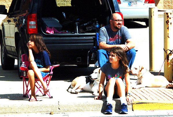 Debbie Blank | The Herald-Tribune<br /> Cherokee Powell (clockwise from left), 9, Sunman, enjoys the procession with dad Scott and sister Elizabeth, 11. With them are Catahoula Zeus (left) and labrador Uke the family adopted the day before.