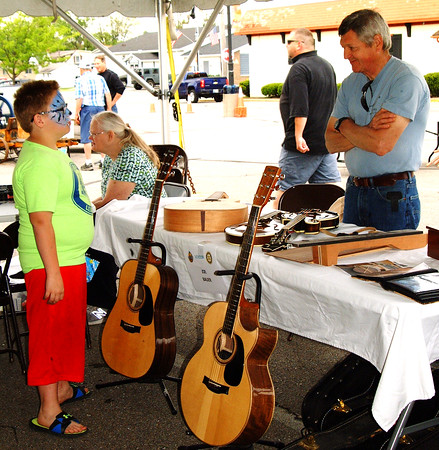 Debbie Blank | The Herald-Tribune<br /> Caleb Flannery (left), 8, Batesville, learns about making musical instruments from Joe Bauer, Peppertown. Bauer estimates it takes about 80 hours to finish a mandolin (on table).