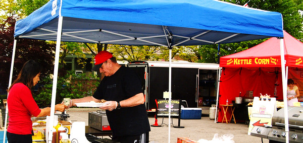 Debbie Blank   The Herald-Tribune<br /> Chi Aune (left), Batesville, buys a pulled pork sandwich from BBQ Street employee Bob Dameron. Kettle corn, homemade ice cream and baked goods were among other treats available at Sawdust Days.