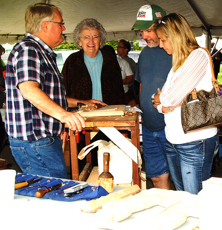 Debbie Blank | The Herald-Tribune<br /> Tim Weberding (from left), Weberding's Carving Shop vice president, discusses the process with sister Mary Ann Struewing, Batesville, friend Steve Quesenberry and niece Amy Jones, Roanoke, Virginia. The third annual Sawdust Days, sponsored by the Batesville Rotary Club, public library, historical society and four businesses, was May 6-7, at the library and downtown.