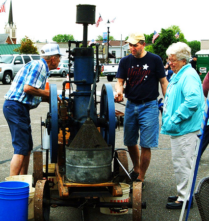 "Debbie Blank | The Herald-Tribune<br /> Denis Schrank (left), Batesville, and son Tim use an International famous nonpareil 4-horsepower gas engine to make ice cream. ""This one is 103 years old,"" reports Denis' wife Pat (right). In earlier days, it would have been a power source to pump water or chop corn for animals."