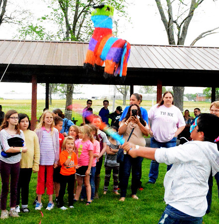 Debbie Blank | The Herald-Tribune<br /> Kids learn about the Hispanic tradition of breaking the pinata. It's tricky with the player blindfolded and the papier mache animal being moved up and down.