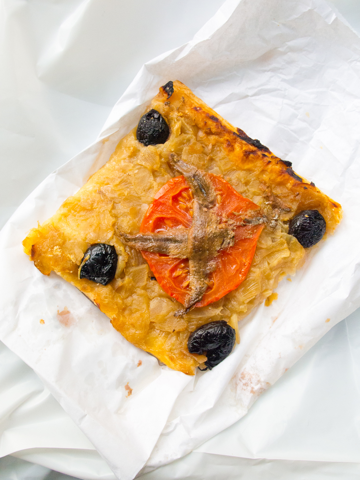 Pissaladière is a typical provencal tart, similar to pizza but traditionally made with onions, anchovies, and black olives. Discover what else to eat in Marseille, the oldest city in France with culinary influences from Spain, Italy and Northern Africa.