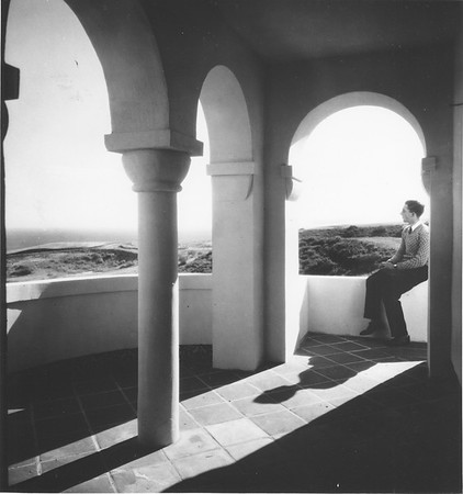 Man sitting on wall of exterior colonnaded area, Villa Aurora, looking out at landscape