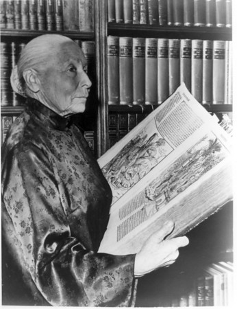 Marta Feuchtwanger holding an open copy of the Nuremberg Chronicle from 1493, ca. 1975-1985