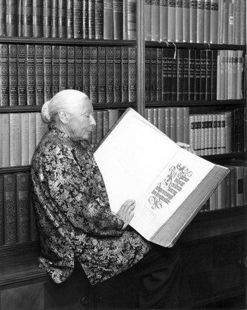 Marta Feuchtwanger holding an open copy of the Nuremberg Chronicle from 1493 (for LA Times), ca. 1975-1985