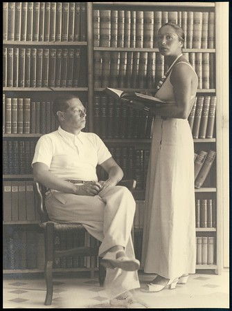 Feuchtwanger sitting in front of two bookshelves in his library in Sanary, with Marta standing next to him, 1933-1939