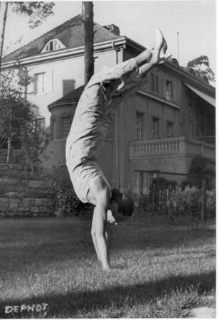 Marta Feuchtwanger doing a handstand on a lawn in Berlin, 1932