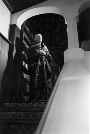 Marta Feuchtwanger stands at the top of the staircase in her Los Angeles home, ca. 1980-1985