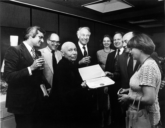 Marta Feuchtwanger stands with a group of friends holding her honorary degree from USC, 1980