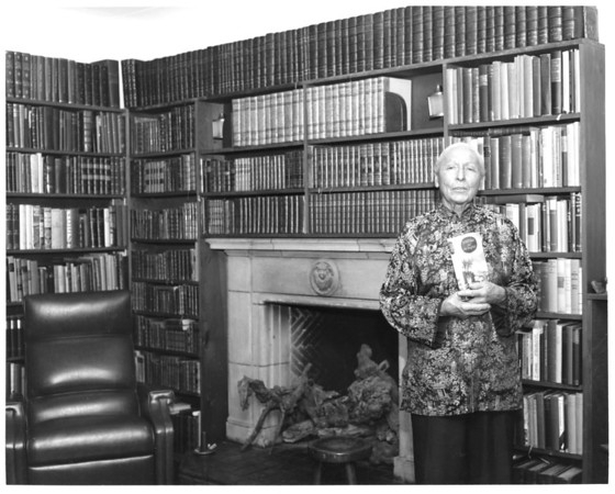 Marta Feuchtwanger in library holding book, ca. 1970-1980