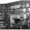Marta Feuchtwanger in library holding book, ca. 1970-1980