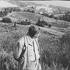 Feuchtwanger standing in front of a hilly vista at Villa Aurora, his head turned slightly toward his left, Pacific Palisades, Calif.