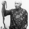 Marta Feuchtwanger holds the end of a snake in her right hand, ca. 1970-1980