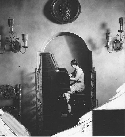 Room with arched entrance to second room, in which a woman is playing an organ, Villa Aurora, ca. 1928