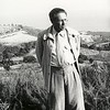 Feuchtwanger standing in front of hilly vista at Villa Aurora, Pacific Palisades, Calif., his body facing the viewer