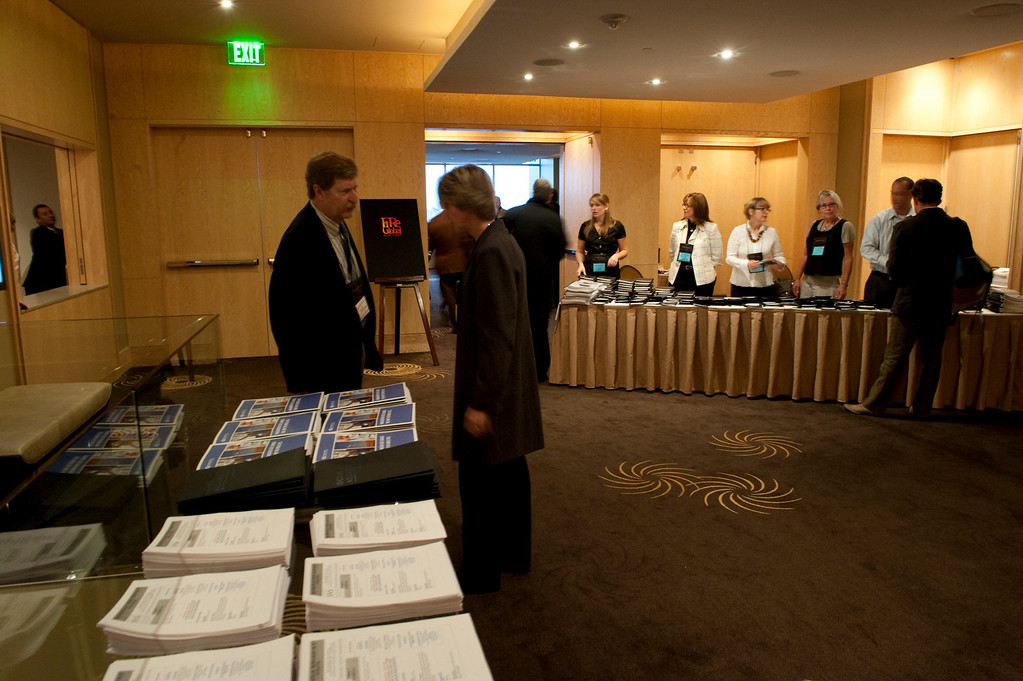 Foreground: Maury Forman (L), Managing Director, ITED, State of Washington Department of Commerce; at tables are SNS staff and volunteers (L-R) Berit Anderson, Nancy Garrison, Ruth Offen, Sally Anderson, and Gustav Toppenberg