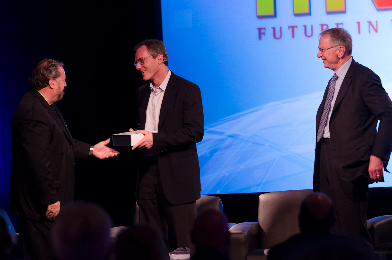 """Host Mark Anderson (L) presents Qualcomm Chairman Paul Jacobs with the FiRe """"CEO of the Year"""" award while Chairman Emeritus Irwin Jacobs looks on.   May 22-25, 2012: At the Montage in Laguna Beach, CA, 200 thought leaders - high technology engineers and executives, entrepreneurs, scientists, and media professionals - gathered for 3 days to participate in FiRe X, the 10th annual Future in Review conference, presented by the Strategic News Service and led by SNS founder and technology visionary Mark Anderson. Interviews, panel discussions, and informal conversations ranged from IP protection to CO2 and climate change, new healthcare paradigms, global economics, ocean toxins, robotics, documentary filmmaking,  medical diagnostics, technology solutions for social issues, global economics, mobile computing, and tech solutions to human trafficking and aging with dignity."""