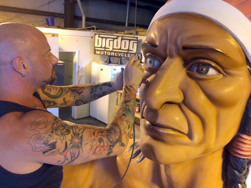 Kurt Robinson of Airbrush Assassians in Marion, Ill, puts final touches on the newly restored Indian Chief Muffler Man back in 2016. This was one of several fiberglass giants manufactured by International Fiberglass Company between 1964 and 1972. (Special to the Reporter-Herald)