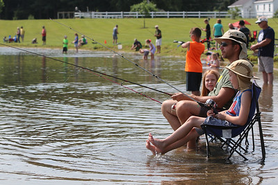 Roger Schneider| The Goshen News This family kept cool by moving their chairs into the shallow water at Fidler Pond Park Saturday. The family was participating in the annual kids and family fishing tournament.