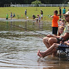 Roger Schneider| The Goshen News<br /> This family kept cool by moving their chairs into the shallow water at Fidler Pond Park Saturday. The family was participating in the annual kids and family fishing tournament.