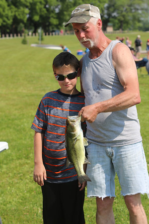 Roger Schneider| The Goshen News<br /> Robert Stowe, 10, of Elkhart, poses with his grandfather, Rom Stowe, after catching an 18-inch largmouth bass during the Fidler Pond Park fishing tournament Saturday.