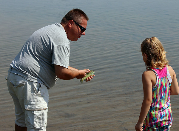 Roger Schneider| The Goshen News<br /> Craig Newcomer explains the markings on a bluegill to his granddaughter Mary Jane Anderson, 6. The two were taking part in the annual fishing tournament Saturday at Fidler Pond Park in Goshen.