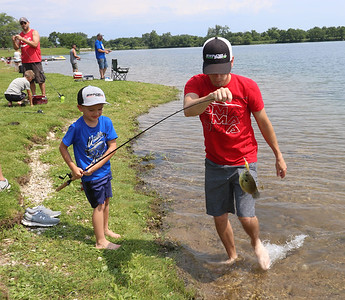 Roger Schneider| The Goshen News Sawyer Hummel, 6, of Goshen, catches a bluegill while his dad Lewie gives him a hand. The father and son were fishing in Saturday's Goshen Parks Department annual fishing tournament at Fidler Pond Park.