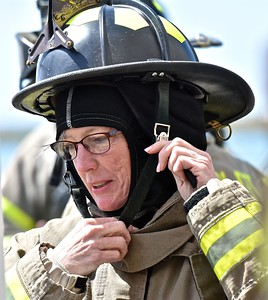 "Fourth District Supervisor Virginia Bass gets herself ready before entering a smoldering ""house"" to experience heavy smoke. (Jose Quezada - For the Times-Standard)"