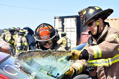 Humboldt Bay Fire Captain Brett Banducci assists a voluteer firefighter how to remove a shatter-proof window. (Jose Quezada - For the Times-Standard)