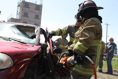 "Eureka City Councilmember Kim Bergel uses the ""jaws of life"" to pry open a car door. (Manny Araujo - Times-Standard)"