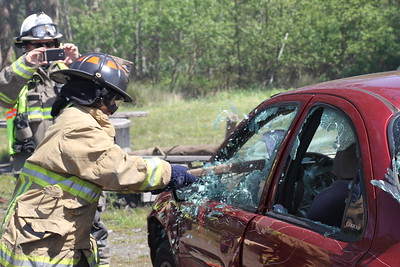 Eureka City Councilmember Kim Bergel smashes the window of a car with an axe. Bergel and other local elected officials participated in a field day with Humboldt Bay firefighters to learn about practices at the authority. (Manny Araujo - Times-Standard)