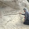 """Participant temporarily carved UNAVCO's name in a sandy bank to practice change detection using SfM method. North Boulder Creek near Cardwell, Montana. (all evidence of carving was removed after the survey).<br /> From short course held at Indiana University Geologic Field Station August 16-19 2016. Short course title: Using TLS and Structure from Motion (SfM) Photogrammetry in Undergraduate Field Education. <a href=""""http://www.unavco.org/education/advancing-geodetic-skills/short-courses/2016/field-education/field-education.html"""">http://www.unavco.org/education/advancing-geodetic-skills/short-courses/2016/field-education/field-education.html</a>"""