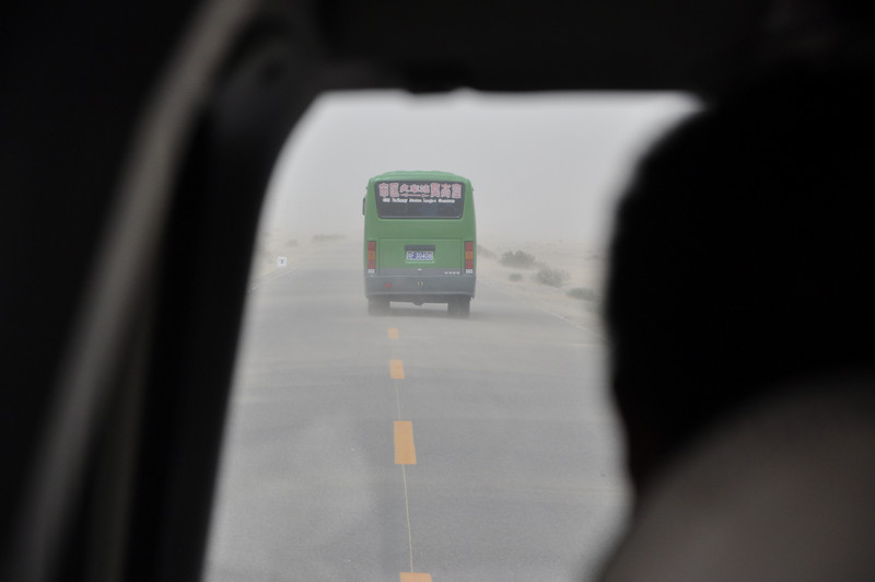 I tried taking a few pictures over our driver's shoulder to catch the sand blowing in sheets across the road...you can see that here, as well as how little visibility there was in the storm!