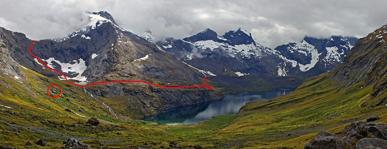 Lake Adelaide and Apirana Peak from the toe of Sabre Peak's north face. The red line indicates the route around the lake and up Gifford's Crack; red circle around Gill's Biv